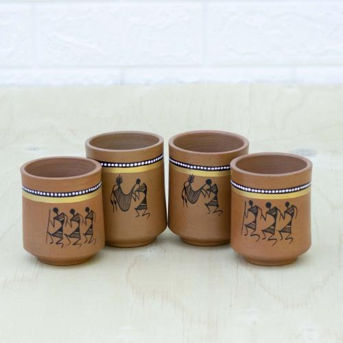 Four brown colored terracotta mugs with Warli art and drawings of traditional tribesmen, placed on a table with a white wall in the background