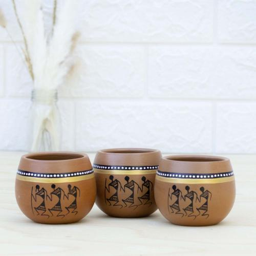 Three terracotta cups with a touch of brown and black colors with tribal paintings, placed on a table with a vase of pampas grass on the left and a white wall in the background
