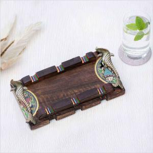 Dark brown wooden tray with fish handles made of brass placed on a white surface next to a glass of water with mint leaves and dried flowers