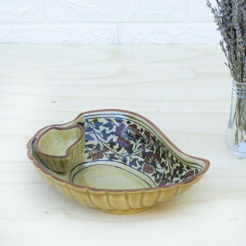 Yellow ceramic abstract bowl with floral design standing on a table with a vase of dried lavender on the right