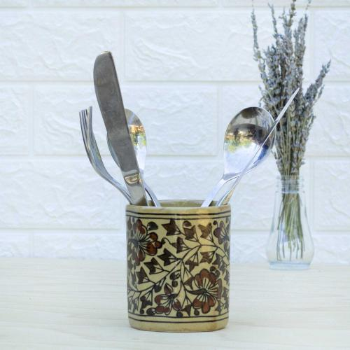 Yellow ceramic cutlery holder with floral design standing on a table with a vase of dried lavender on the right