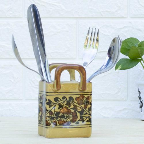 Yellow ceramic cutlery holder with floral patterns standing on a table with a vase with green leaves on the right