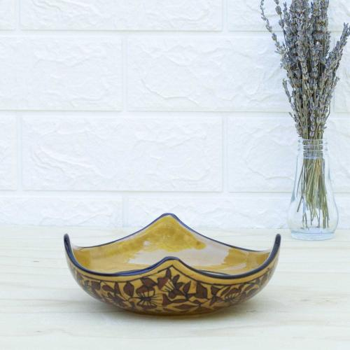 Yellow ceramic bowl with floral design standing on a table with a vase of dried lavender on the right