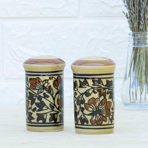 Two yellow salt and pepper set with floral design standing on a table with a vase of dried lavender on the right