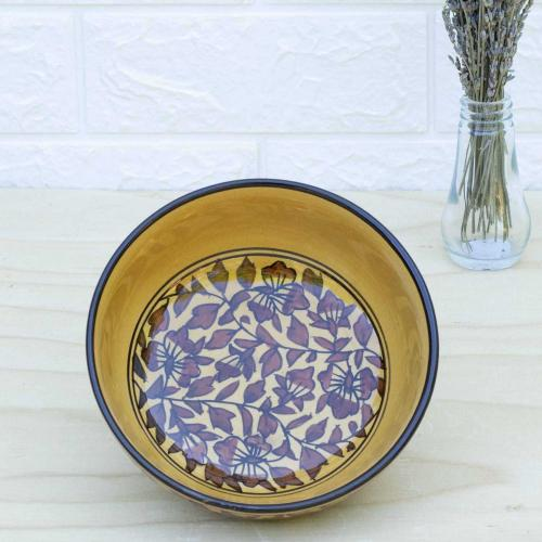 Yellow ceramic set of  bowls in different shapes with floral design standing on a table with a vase of dried lavender on the right