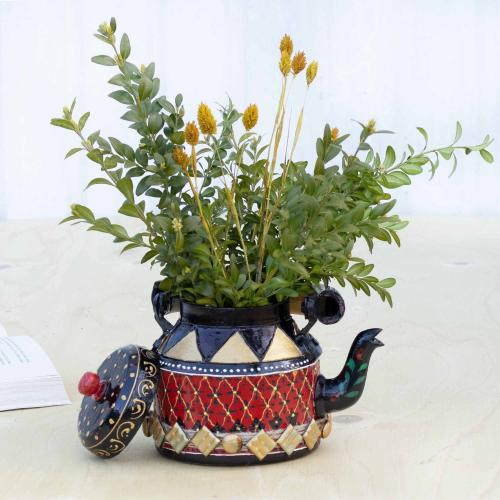 Teapot shaped planter filled with golden oats standing on a table with an open book to the left in the background