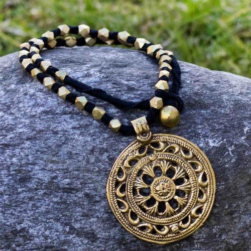 Bohemian style necklace with brass beads and a flower shaped pendant tied in black thread
