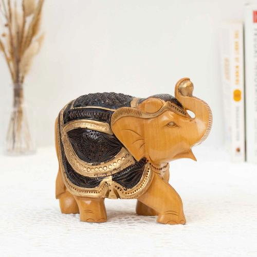 Wooden elephant figurine in black and gold colors placed on a white surface with books and a vase of dried flowers in the background.