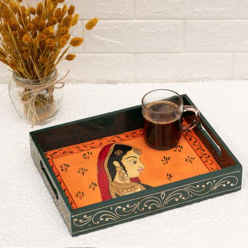 Wooden tray in orange color and black borders portraying a queen with ornaments carrying a cup of coffee placed on a white surface with a vase of dried flowers and a white wall in the background.