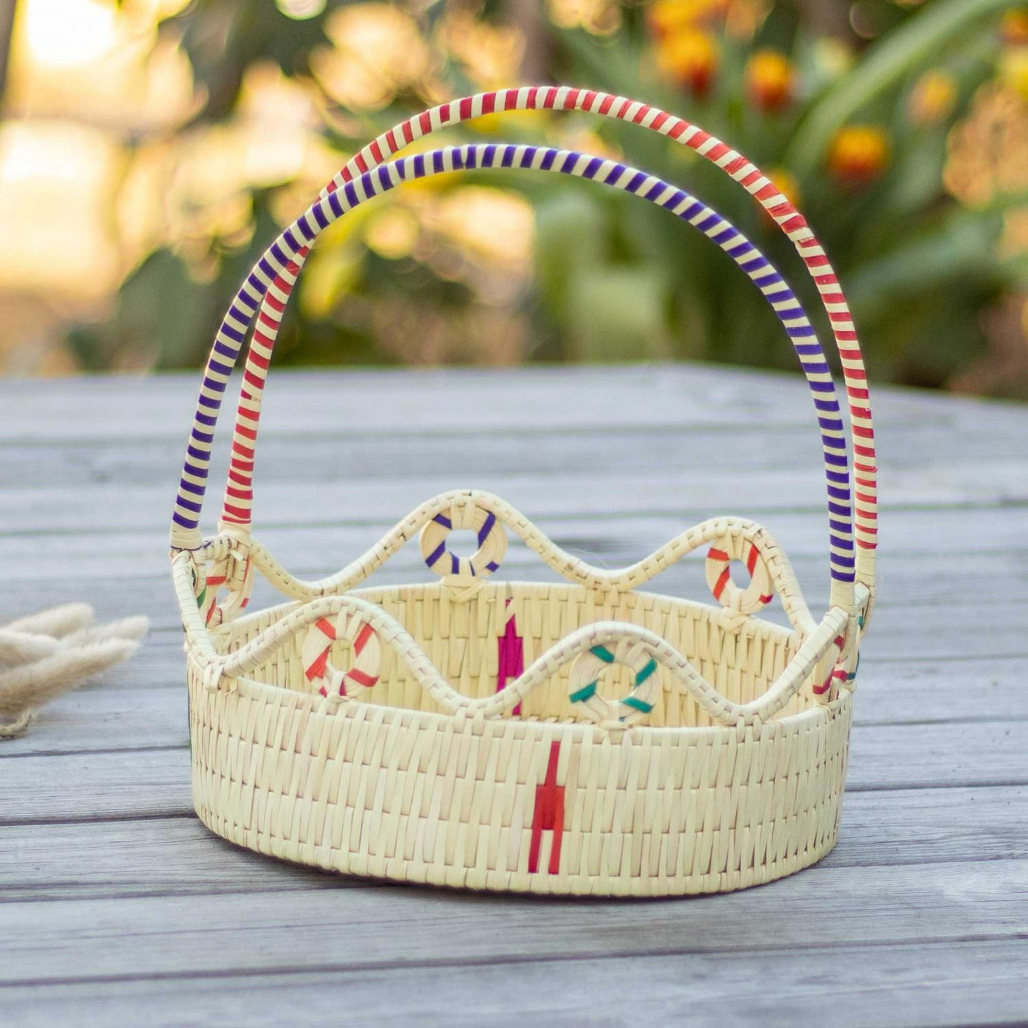 Palm leaf and golden grass basket with red and blue handle