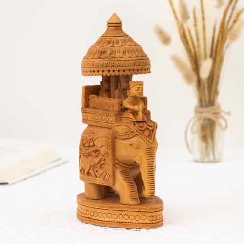 Wooden elephant figurine with an umbrella and detailed carvings placed on a white surface with an open book and a vase of dried oats in the background.