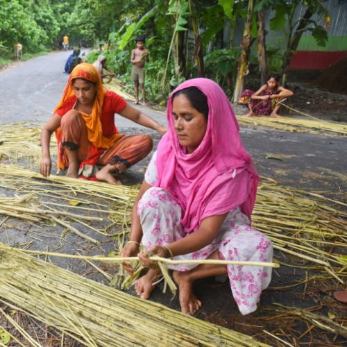 Two women in colorful clothes sitting on a road working on processing jute stalks