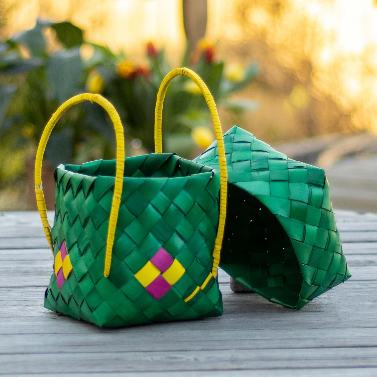Bright green palm leaf box with pink handle and a small decoration in yellow and pink
