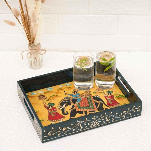 Colorful wooden tray with black borders depicting a king on an elephant surrounded by his guardsmen carrying two glasses of water with green leaves placed on a white table with a vase of dried oats and a white wall in the background.