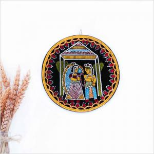Black wall art with colorful patterns illustrating an indian wedding hanging on a white wall next to a vase with dried oat leaves