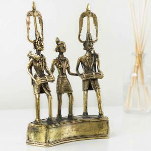Brass figurine of three tribesmen playing music and dancing