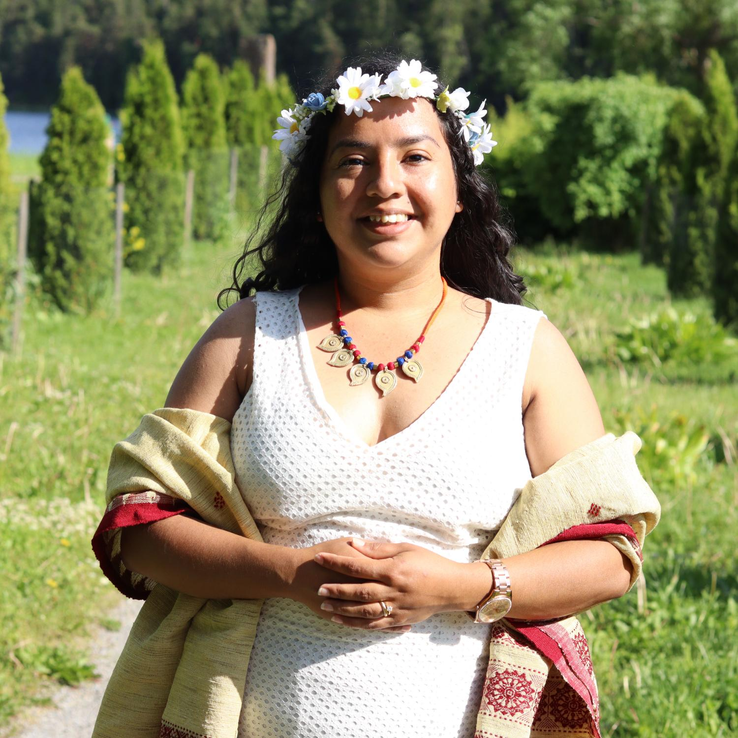 Woman in a white dress standing on a path in a green park wearing a light yellow shawl with red trim, a necklace small brass leaves and white flower wreath on her head