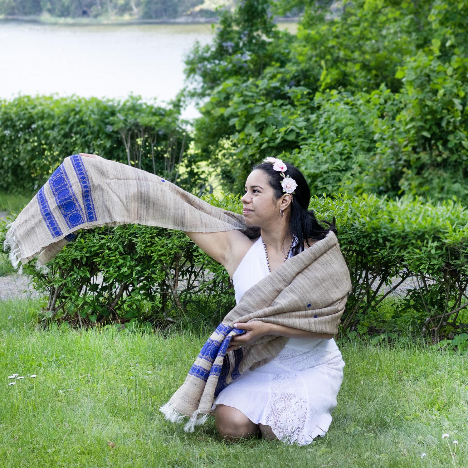 Woman in a white dress and beige gray shawl with blue pattern border sitting on the grass in a park