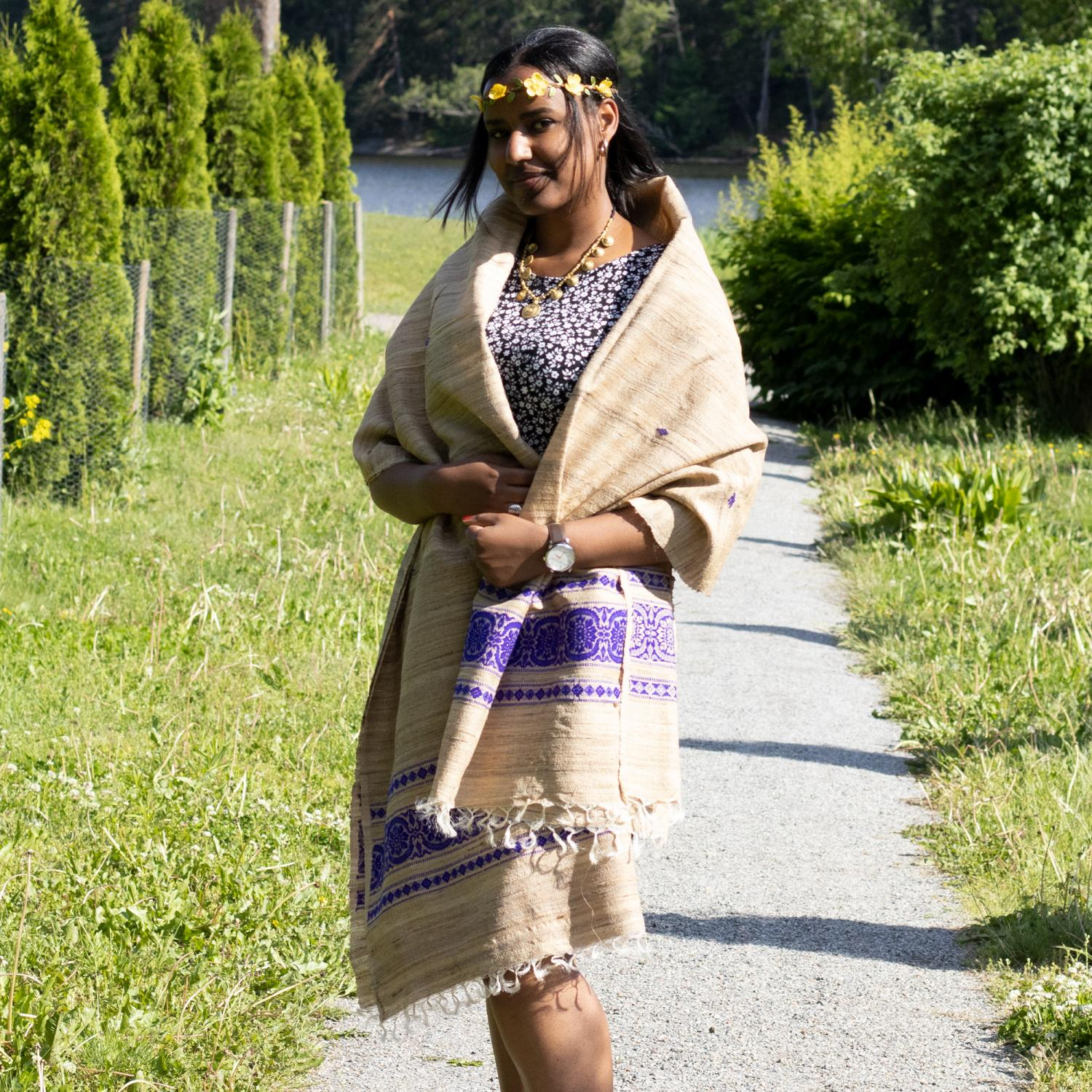 Woman in dark floral dress wrapped in a shawl with purple pattern edge, walking on a path in a park
