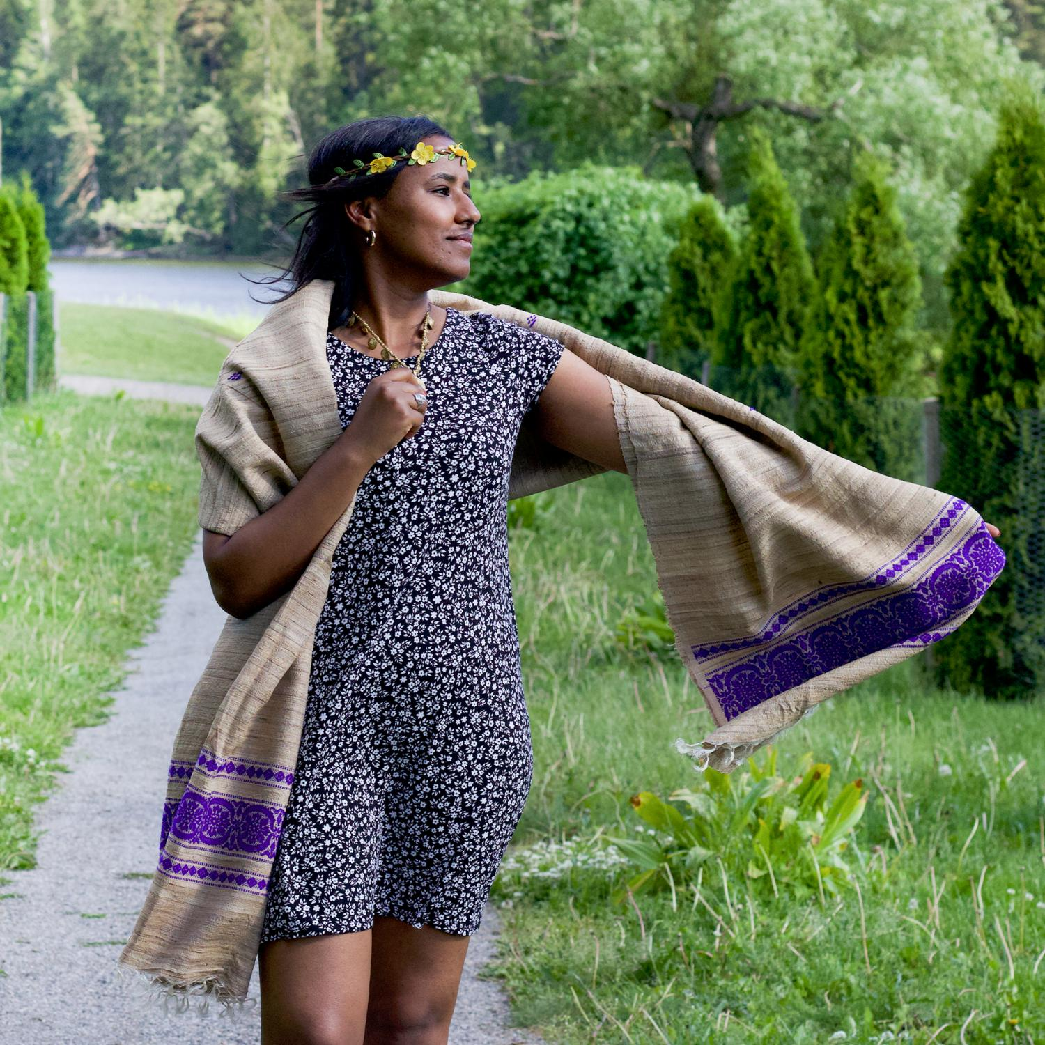 Woman in dark floral dress and shawl with purple pattern edge standing on a path in a park with one arm outspread and the opposite hand holding a necklace