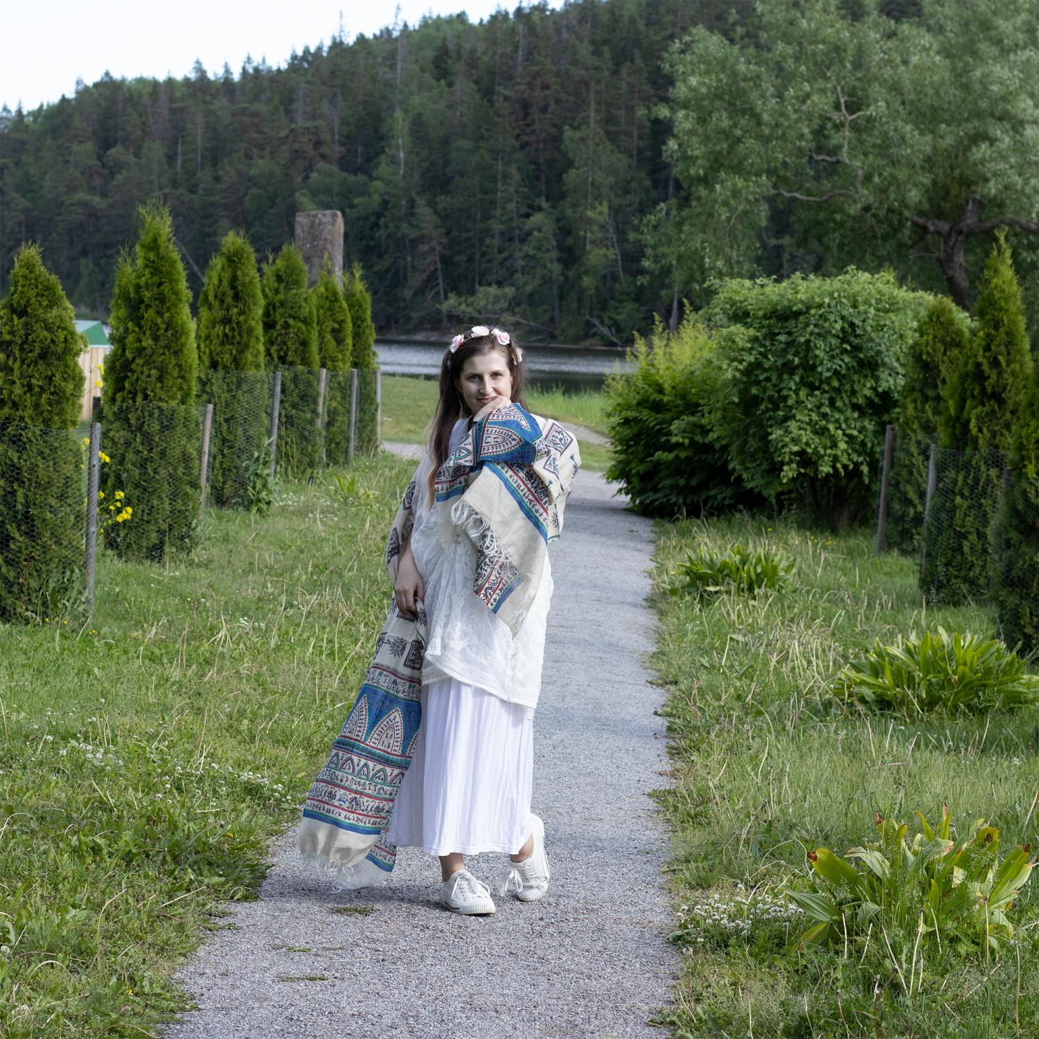 Woman in a white clothes on a path in a green park wearing a shawl blue shawl with tribal pattern and light pink wreath on her head