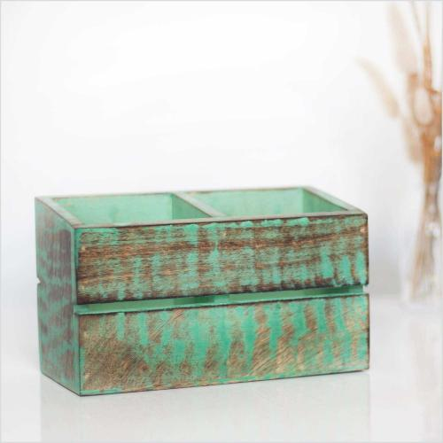 Mango wood cutlery holder in rustic green acrylic paint standing on a table with a vase filled with dried pampas grass in the background