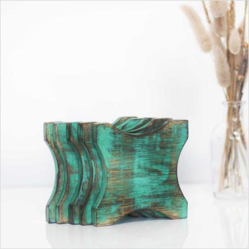 Mango wood coasters in rustic green color standing on a table with a vase filled with dried pampas grass