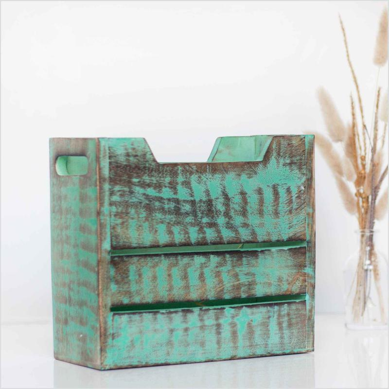 Newspaper stand of mango wood in rustic green color standing next to a vase filled with dried pampas grass