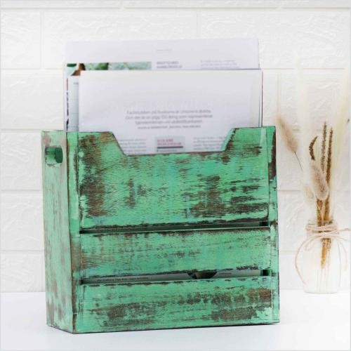 Newspaper stand of mango wood in rustic green color filled with paper that stands next to a vase with dried pampas grass