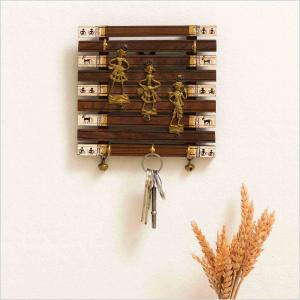 Warli wooden key holder with a brass motif at the centre of musicians and the keys hanged on the hooks