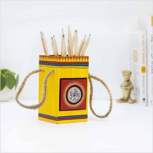 Wooden pen stand in mustard and red color with tribal motifs holding pencils placed on a white surface with a green plant, brass figurine and books in the background