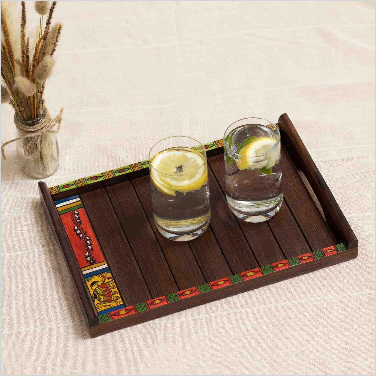 Wooden tray with colorful painted edge with tribal motifs and handles carrying two glasses of water with lemon and mint placed on a white surface next to a vase of dried flowers.