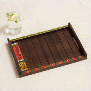 Wooden tray with colorful painted edge with tribal motifs and handles placed on a white surface next to a glass of water with lemon and mint.