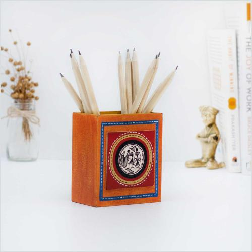 Orange pen stand with colorful dotted lines and tribal art holding pencils and standing on a white surface with a brass figurine, dried flowers and books in the background
