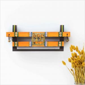 Orange towel hanger with brass bells and tribal motifs hanging on a white wall next to a vase with dried flowers