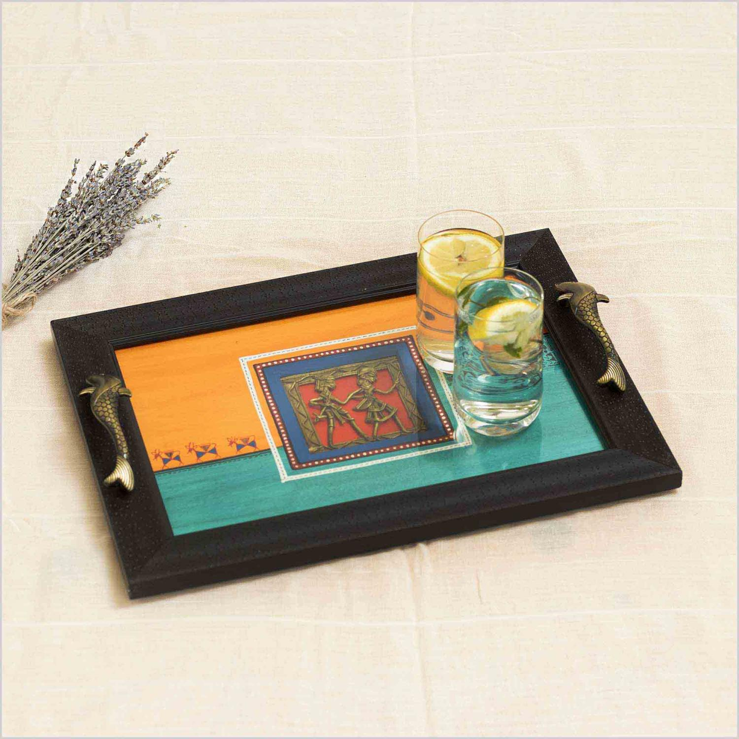 Wooden Tray with a glass on two lemon water on the base of orange and blue and brass motif at the centre with fish handles and warli dancing picture