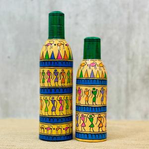 Decorative bottles with tribal motifs and patterns in yellow, purple, pink and green color with blue stripes standing on a table with a beige table cloth and a grey background