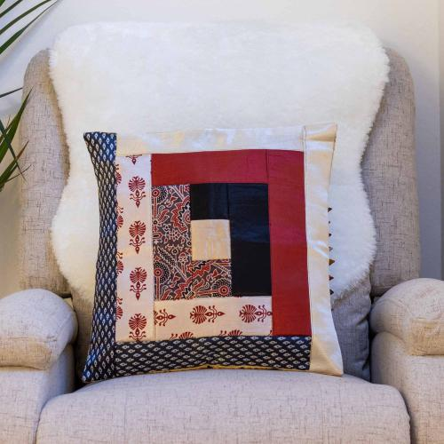 Mashru silk cushion cover with patchwork pattern in Ajrak print in red, off-white, and black