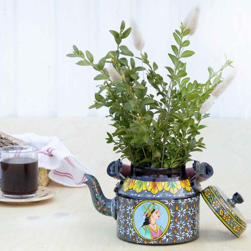 Aluminium planter with a portrait of a king decorated with a touch of metal paints on a table with a glas coffee cup and bread basket in the background to the left