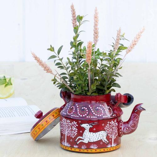 Aluminium planter featuring a gazelle on a deep red background filled with green twigs standing on a table with a book and a glass in the background