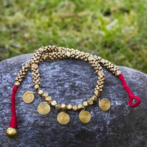 Brass necklace on red string with coin shaped discs and brass beads