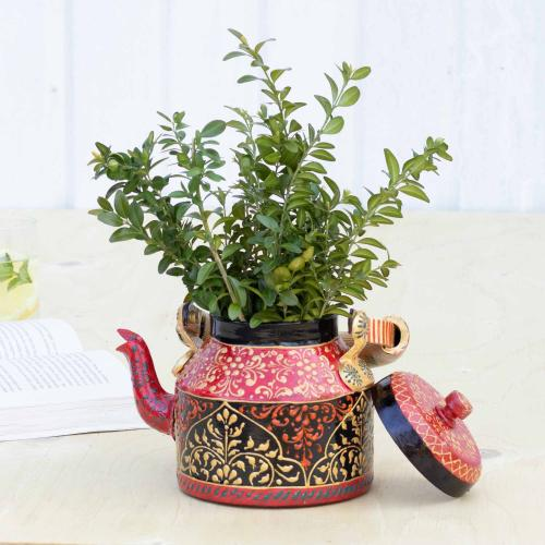 Teapot shaped planter filled with green leaves standing on a table with a book and a glass in the background