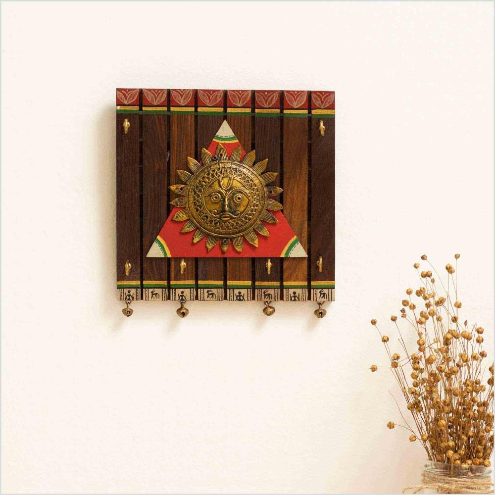 Wooden key holder with a brass motif of sun with hooks and brass bells with a vase of dried flowers