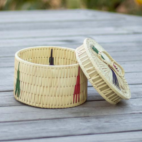 Palm leaf jewelry box with the touch of pink, blue, green and comes with handles.