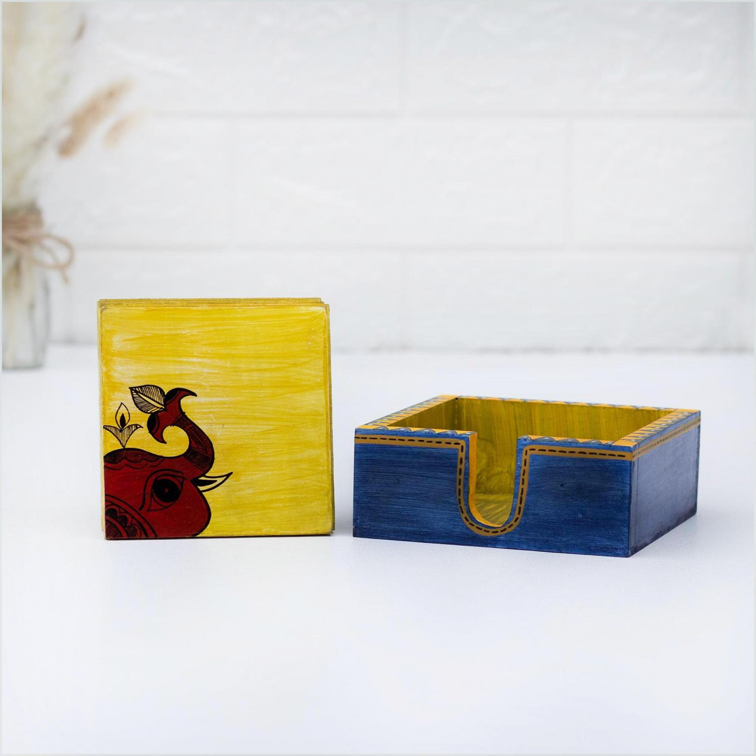 Wooden coaster set in yellow color with an elephant motif standing next to a blue and yellow holder on a white table with a white wall and dried flowers in the background