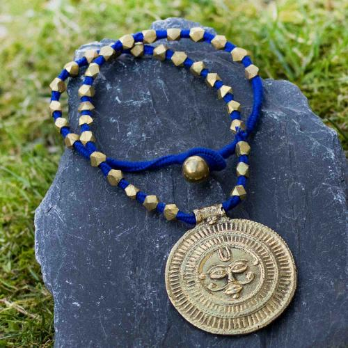 Brass pendant on a cobalt blue string with geometric beads