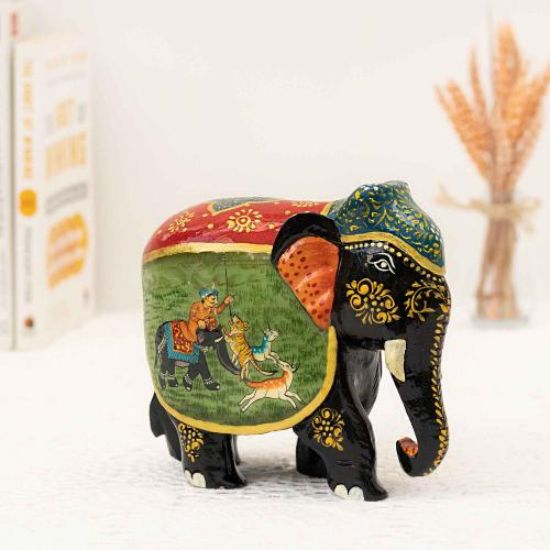 Elephant figurine with a mix of colors and a painting of a man on a hunt placed on a white surface with books and a vase of dried flowers in the background.