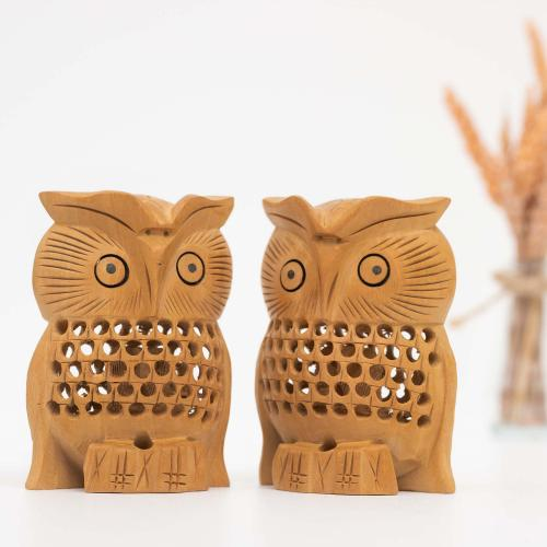 Two wooden owl figurines with mesh work placed on a white surface with a vase of dried oats in the background