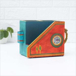 Cutlery holder in orange and blue color with green borders along with brass handles placed on a white table with a white wall and a green plant in the background