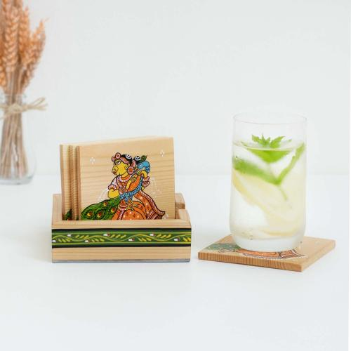 Coasters with a tribal girl print on a beige base with a green leaf print on the holder with a glass of water placed on a coaster and a vase with dried flowers on a white background